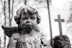 Statue of little boy Angel at Rasu cemetery in Vilnius, Lithuania. Black and white image