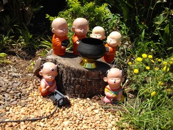 Statue of little monk standing on wooden with two children sitting on the stone with nature background.