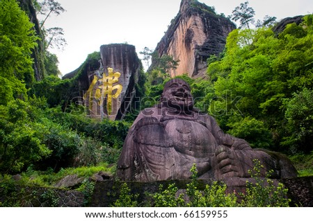 Statue of lucky Buddha, symbol of Buddhism (fo) carved in the mountain