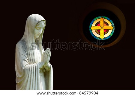 Statue of Mary praying in profile with isolation path and out of focus cross shaped window on the right