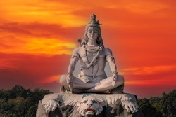 Statue of meditating Hindu god Shiva against the red sky on the Ganges River at Rishikesh village in India, close up