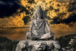 Statue of meditating Hindu god Shiva against the sky and clouds on the Ganges River at Rishikesh village in India, close up