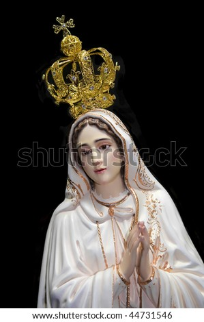 Statue of Our Lady of Fatima over black background.