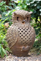 Statue of owls in the beautiful green garden background