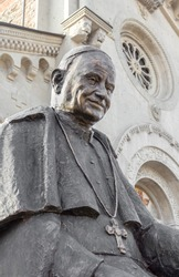 Statue of Pope John XIII with an Italian church in the background