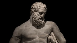 Statue of powerful Hercules, closeup, isolated at black background, details