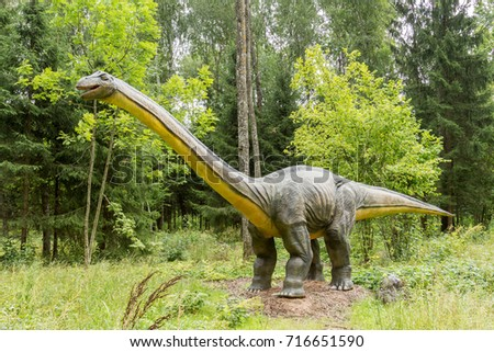 Statue of realistic Diplodocus dinosaur in a wild forest