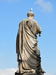 Statue of Saint Peter from the back on Vatican square with a bird sitting on its head. Blue sky with white clouds are in the background.