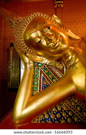 Statue of sleeping Buddha covered in gold paint and gold leaf in a local Thai temple