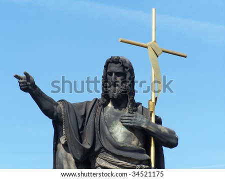 Statue of St. John the Baptist with golden cross, Charles bridge, Prague, Czech Republic