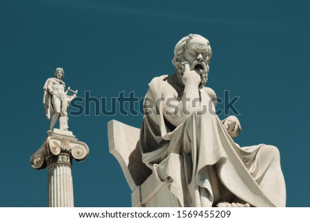 Statue of the ancient Greek philosopher Socrates in Athens, Greece, with the statue of the ancient Greek God Apollo in the background.