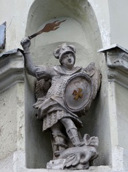 Statue of the angel Saint George with wings behind his back and the flaming sword of the victorious dragon. Stone figure in a niche of an old building