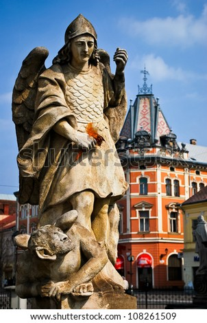 Statue of the Archangel Gabriel with historic building in the background
