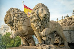 Statue of the goddess Cibeles and the lions in the city of Madrid, Spain, during a sunny summer day with few clouds