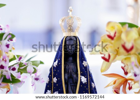 Statue of the image of Our Lady of Aparecida, mother of God in the Catholic religion, patroness of Brazil, decorated with flowers and orchids
