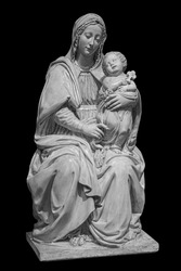 Statue of the virgin Mary carrying the baby Jesus isolated on black background. Mother of god sculpture, classic christian art