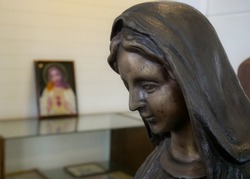 Statue of the Virgin Mary on blurred background with Jesus Christ picture.