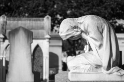Statue of weeping woman on a grave (black and white) in a cemetery