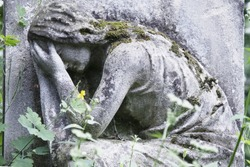 Statue of woman on tomb as a symbol of depression pain and sorrow (faith, religion, Christianity, death concept)
