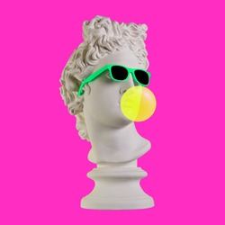 Statue on a pink background. Gypsum statue of Apollo head. Man. Creative. Plaster statue of Apollo head in sunglasses. Minimal concept art.