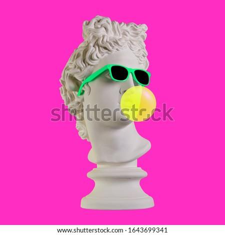 Statue on a pink background. Gypsum statue of Apollo head. Man. Creative. Plaster statue of Apollo head in sunglasses. Minimal concept art.