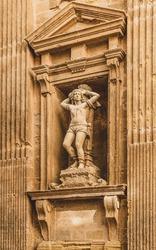 Statue on the façade of the Baroque cathedral of Sant'Agata built in the 17th century, Gallipoli, Salento, Puglia region, Italy. Facade decorated in carparo, a local limestone-