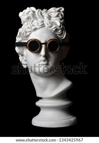 Statue. Plaster statue of Apollo's head.  Creative. Plaster statue of Apollo with antique glasses. Head. Coronavirus. Coronavirus Covid-19 outbreaking. Apollo Belvedere