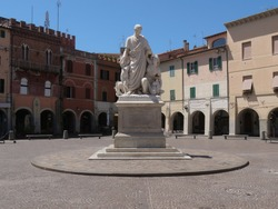 Statue to Canapone is a white marble sculpture on a basement, it is in the center of Piazza Dante in Grosseto and it represents a man looking at a woman holding a child.