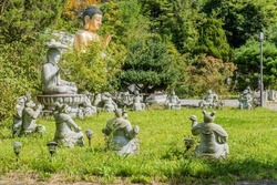 Statues of animals of Chinese horoscope and seated stone and bronze Buddha in garden of Buddhist temple.