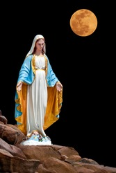 Statues of Holy Women on piles of limestone rocks isolated on black background with clipping path.