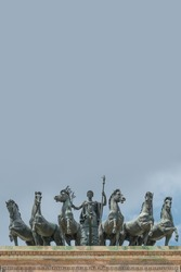 Statues of 6 horses and Goddess Victoria at the top of Triumphal Arch called Arch of Peace (Porta Sempione) in Milan historical downtown, Sempione Park, Italy, with copy space