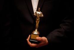 Statuette in hands. Winner holding their award