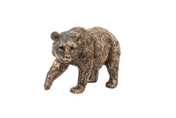 Statuette of a bronze bear with a raised paw looking at the camera, isolated on a white background