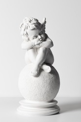 Statuette of a sleeping angel on a white background