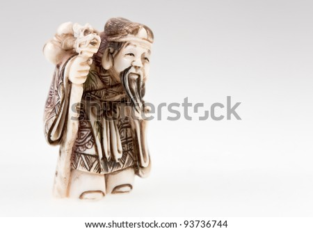 statuette of Chinese  god of wealth - Tsai Shen on grey background - stock photo
