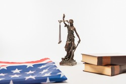 statuette of justice near american flag and books isolated on white