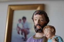 Statuette of Saint Joseph with sleeping Baby Jesus and a picture of Father and Daughter on the Background