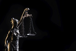 Statuette of the goddess of justice Themis with scales - isolated on black background. Law concept