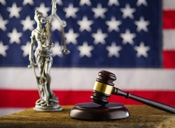 Statuette of Themis, judge's gavel on the background of the American flag. Court, justice, equality of law, punishment for crimes, presumption of innocence. Advertising, poster, banner.