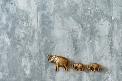 statuettes of copper elephants walking one after another are taken on a gray background, gold figures of Indian elephants, bronze animals in miniature