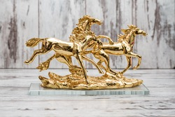 Statuettes of golden horses on white wooden background