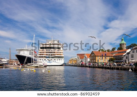 STAVANGER, NORWAY - JULY 15: Two luxury cruise ships moored in the port of Stavanger. Queen Mary 2 is 345m long and a capacity of 2600 people. AIDA Blu 252m long on July 15, 2011 in Stavanger, Norway.