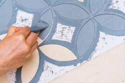 Stay at home and home improvement concept: Close up and top view of a hand holding a brush is painting a decorative template on the floor tiles into gray by using a vintage pattern stencil