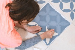 Stay at home and home improvement concept: Close up and top view of a woman holding a brush to paint a decorative template on the floor tiles into gray by using a generic turkish pattern stencil