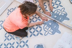 Stay at home and home improvement concept: Top view of a woman painting with a brush a decorative template on floor tiles in gray by using a generic turkish pattern stencil. Reflection in mirror