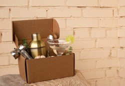 Stay at home bar cocktail party. Classic Margarita cocktail and bartender stuff parcel in a brown craft cardboard box. Gift to mixology lover. Beige brick wall background. Tender retro hipster colors.