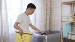 stay-at-home good looking dad pressing buttons on washing machine while doing laundry for family in home laundry room.