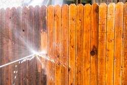 Stay at Home house repairs , Pressure Washing Fence with a high pressure washer , cleaning old dirty planks of wood on Wooden Fence in Suburb Neighborhood