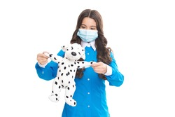 Stay at home. Little child in medical mask play with toy dog. Fighting against SARS-CoV-2. Preventing covid-19 transmission. Atypical viral pneumonia. Coronavirus infections. Stay home. Save lives.