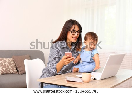 Photo of Stay at home mom working remotely on laptop while taking care of her baby. Young mother on maternity leave trying to freelance by the desk with toddler child. Close up, copy space, background.
